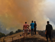Villagers gather as smoke billows from a fire in the forested hills of the Kabylie region, east of the Algerian capital Algiers, on August 12, 2021. Ryad KRAMDI / AFP