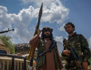 Afghan armed men supporting the Afghan security forces against the Taliban stand with their weapons and Humvee vehicles at Parakh area in Bazarak, Panjshir province on August 19, 2021. Ahmad SAHEL ARMAN / AFP
