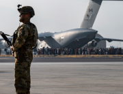 In this image courtesy of the US Air Force, a US Air Force security forces raven, assigned to the 816th Expeditionary Airlift Squadron, maintains a security cordon around a US Air Force C-17 Globemaster III aircraft in support of Operation Allies Refuge at Hamid Karzai International Airport (HKIA), Kabul, Afghanistan, on August 20, 2021. Taylor Crul / US AIR FORCE / AFP