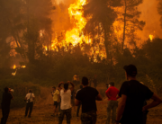 A local uses a megaphone as others observe a large forest fire approaching the village of Pefki on Evia (Euboea) island, Greece's second largest island, on August 8, 2021. ANGELOS TZORTZINIS / AFP
