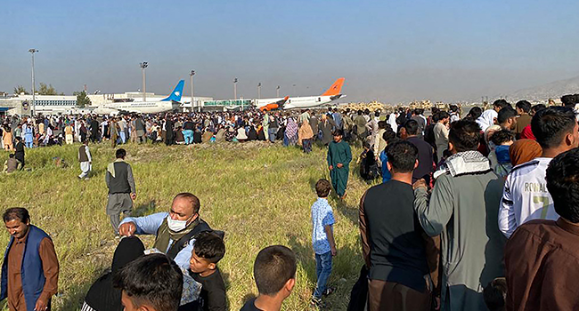 Afghans crowd at the airport as they wait to leave from Kabul on August 16, 2021. Shakib Rahmani / AFP