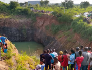 A crowd gathers at the site of an excavation pit where a vehicle was said to have plunged into on August 14, 2021.
