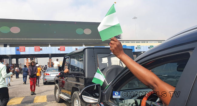 PHOTOS: Youths Defy Heavy Security Presence, Blare Horns, Wave Flags At Lekki Tollgate