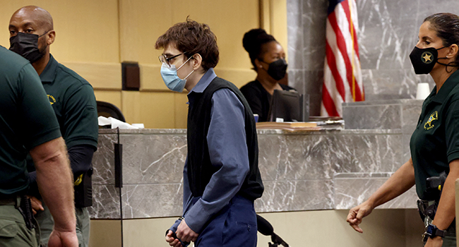 Marjory Stoneman Douglas High School shooter Nikolas Cruz crosses the courtroom in handcuffs at the Broward County Courthouse after being sentenced on four criminal counts stemming from his attack on a Broward County jail guard in November 2018, on October 20, 2021 in Fort Lauderdale, Florida. Amy Beth Bennett-Pool/Getty Images/AFP