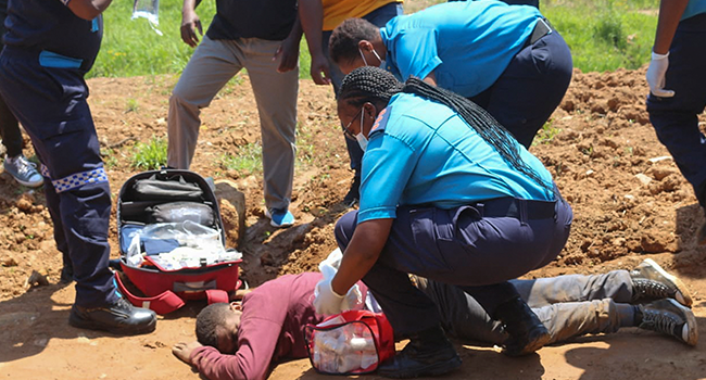 Paramedics tend to a person who was injured by police during protests in Mbabane on October 20, 2021. AFP